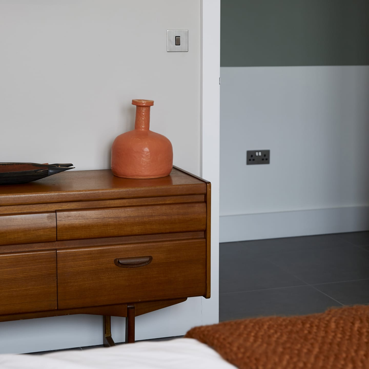 Wooden draws in a neutral bedroom with orange features