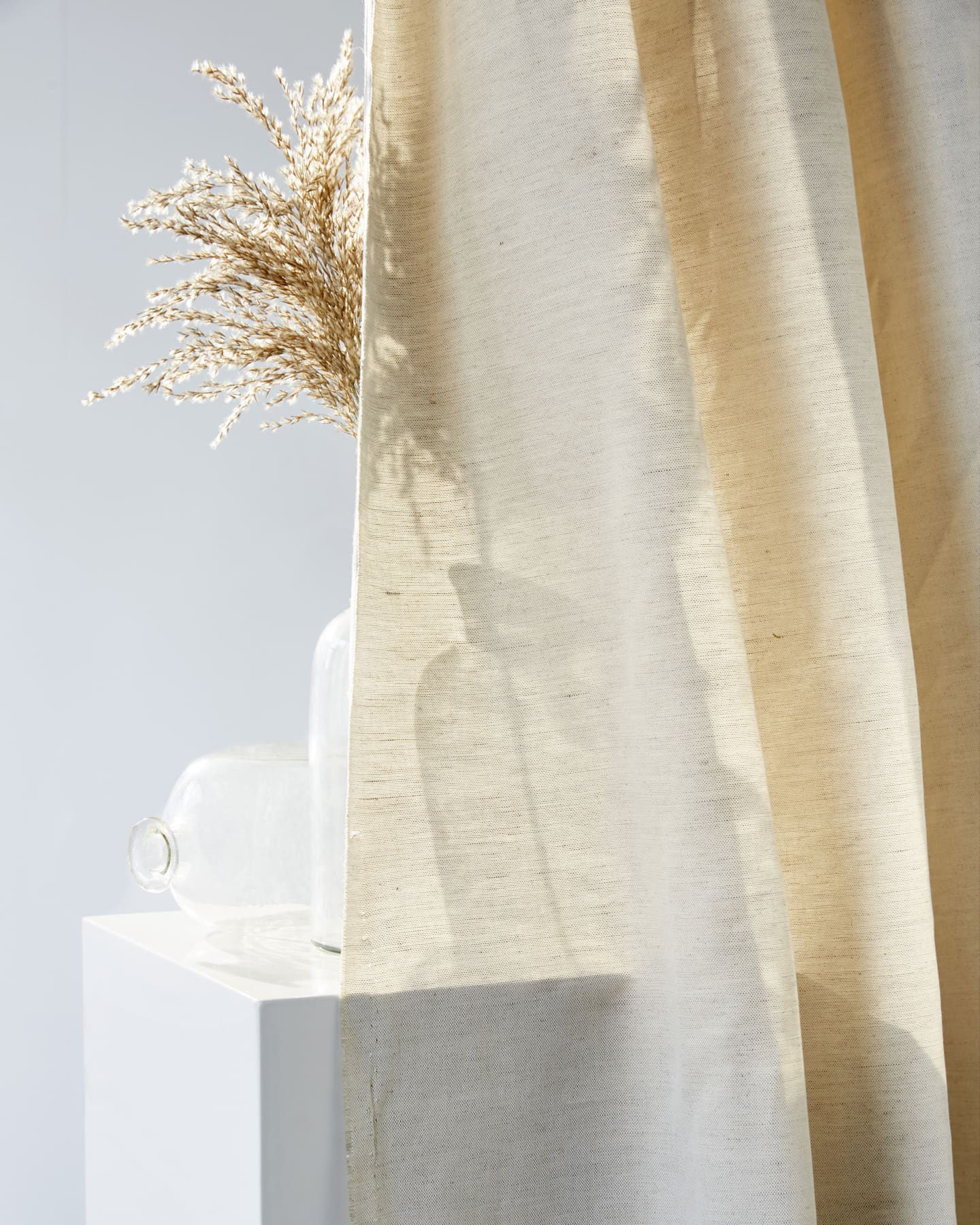 Nude curtain next to vase of grain