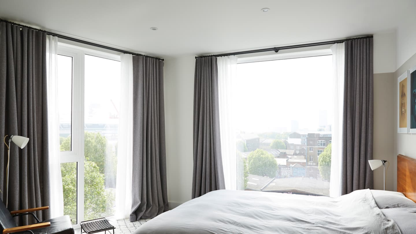 grey curtains open in bedroom