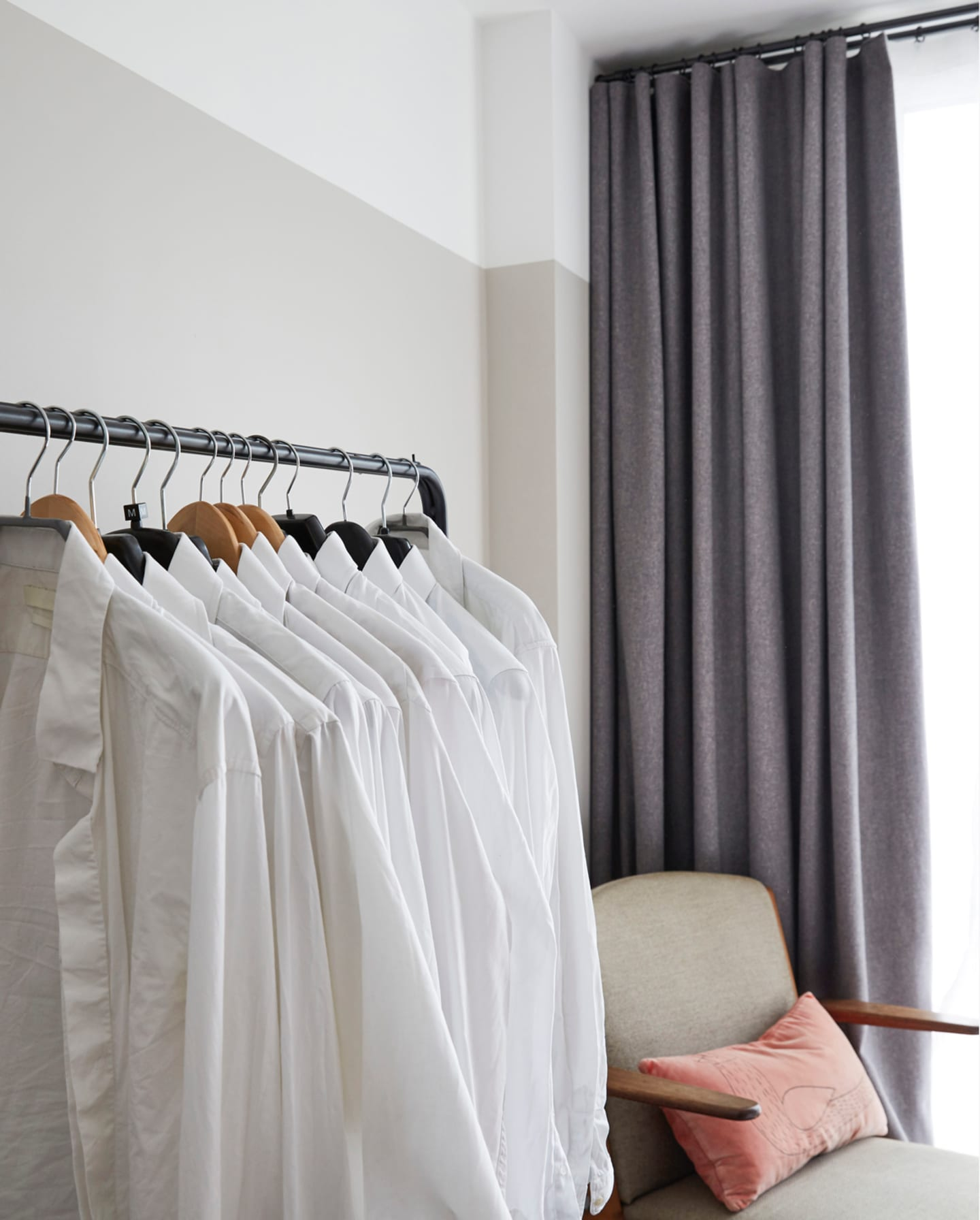 White shirts on a cloths rack, with grey fabric on the background.