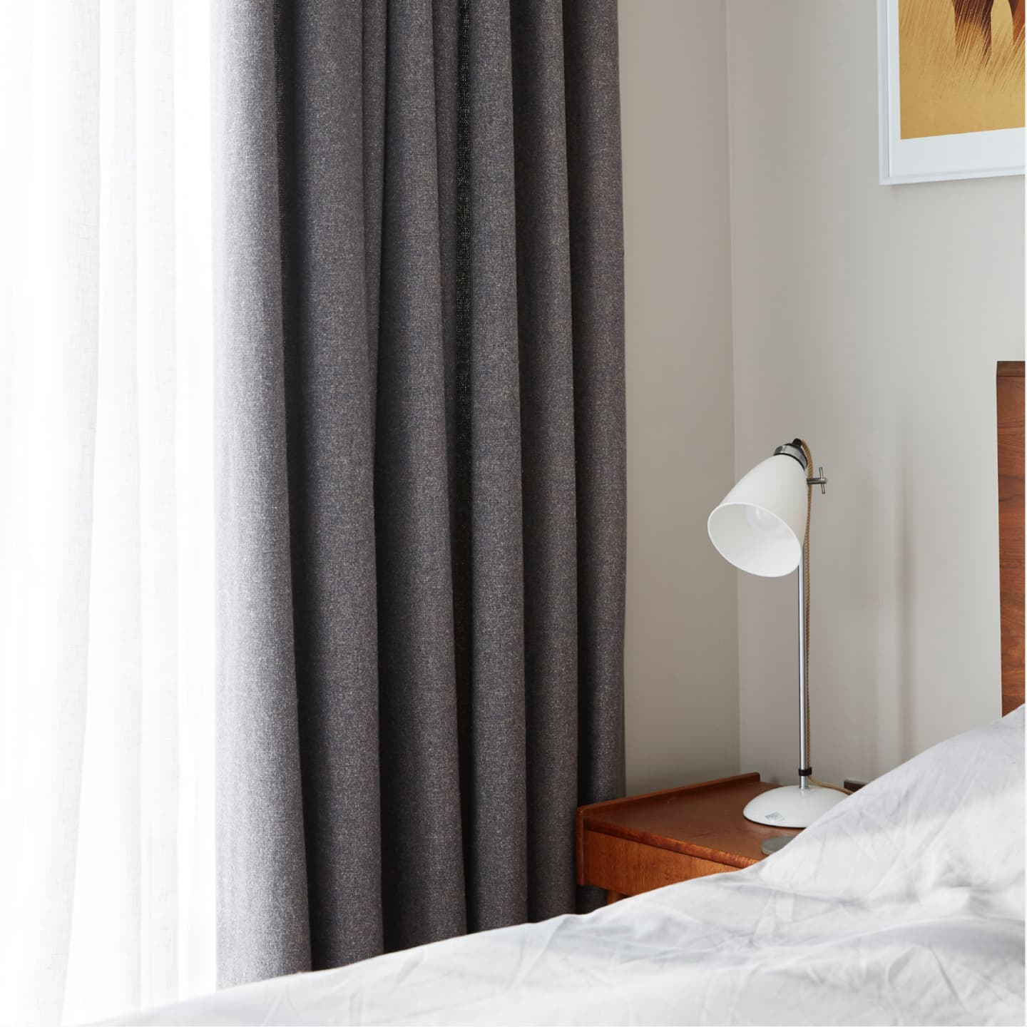 bedside table + light with grey curtains