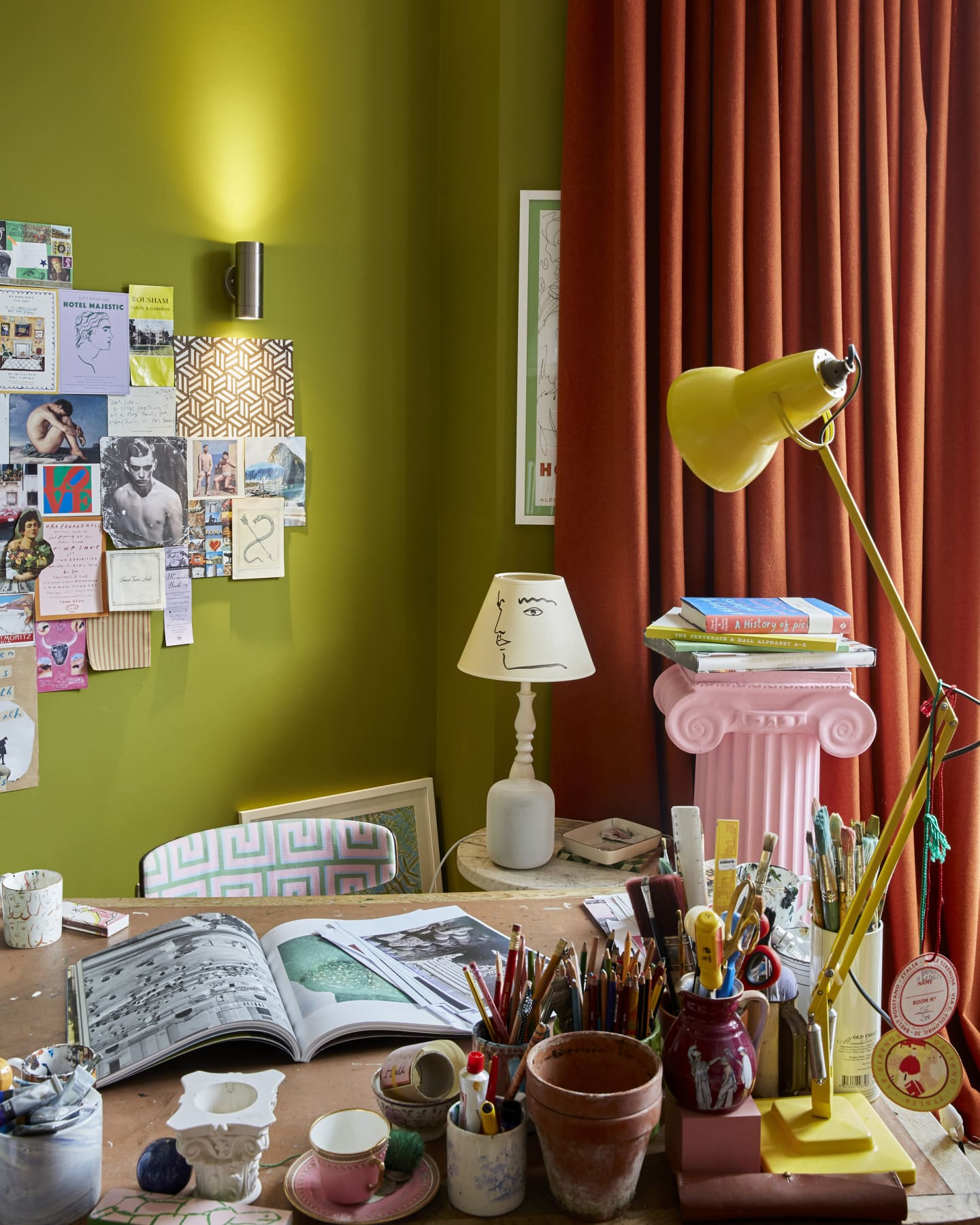 Messy books and several lamps on a table