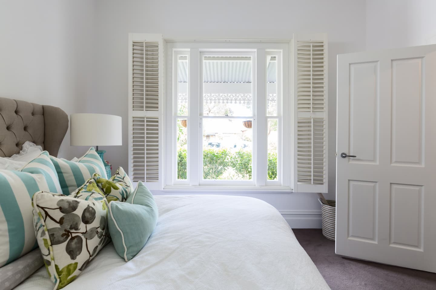 Bedroom with open white shutters