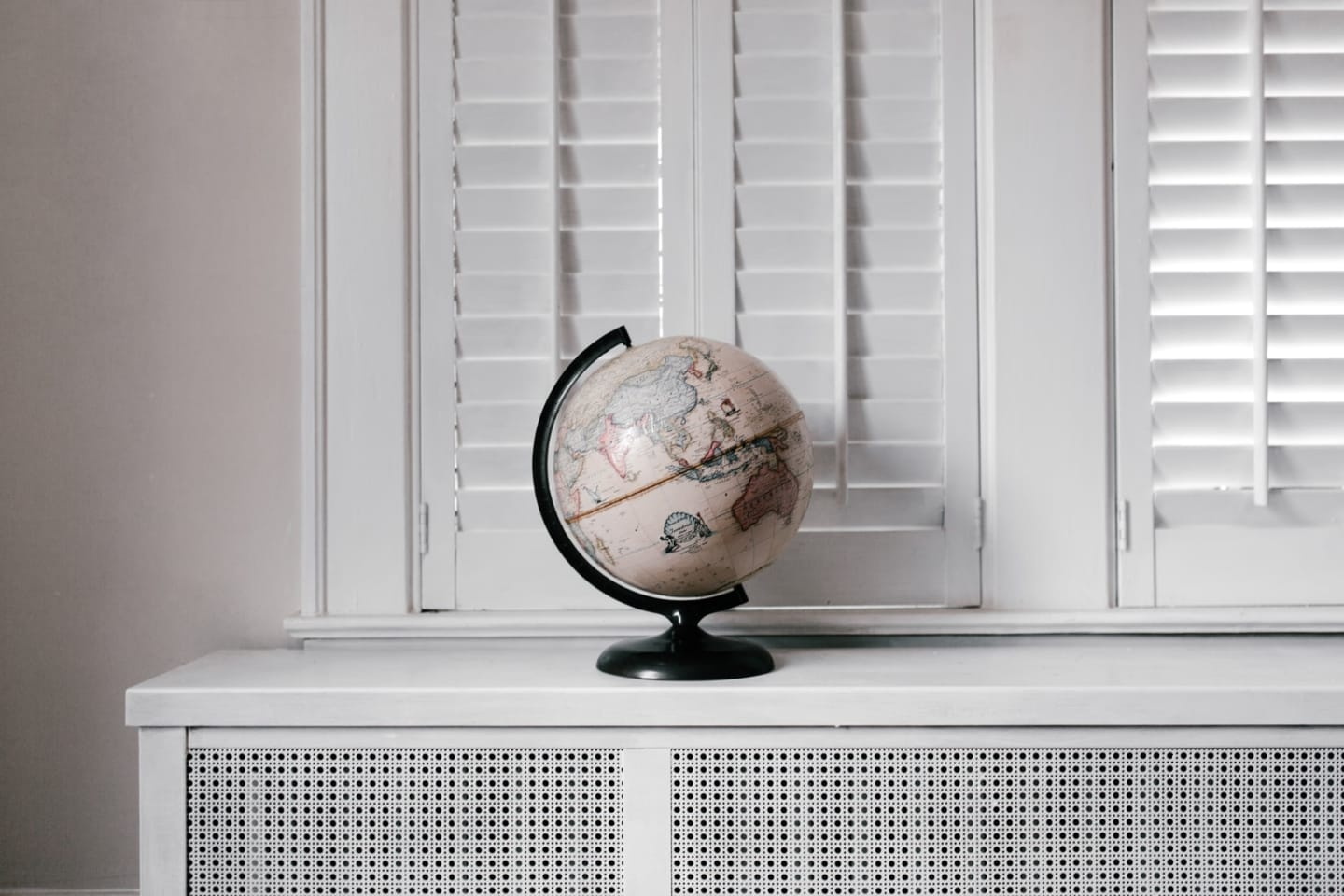 globe on shelf next to white shutters