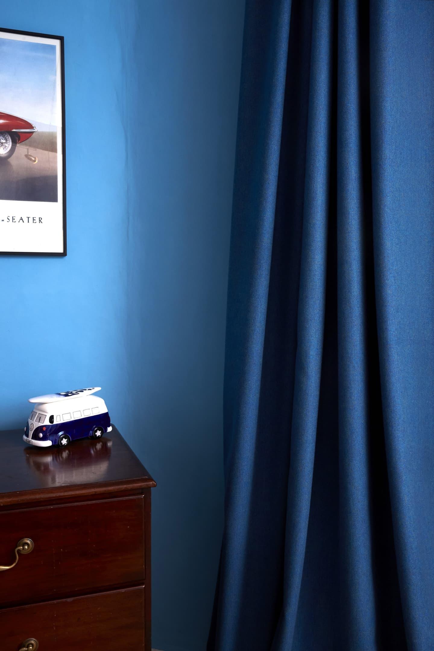Navy blue curtain and dark wooden draws