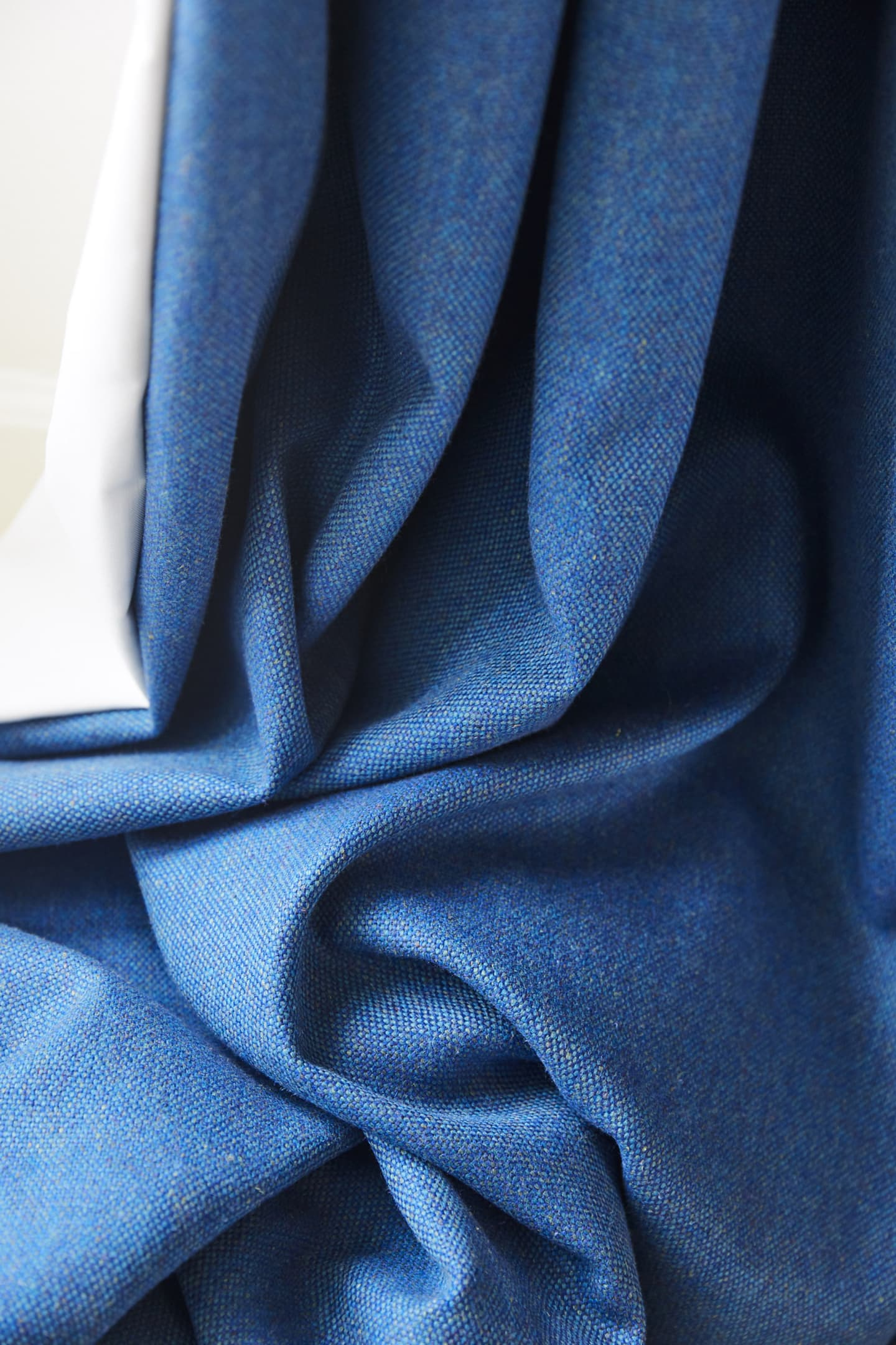 close up of creased blue curtain stitching