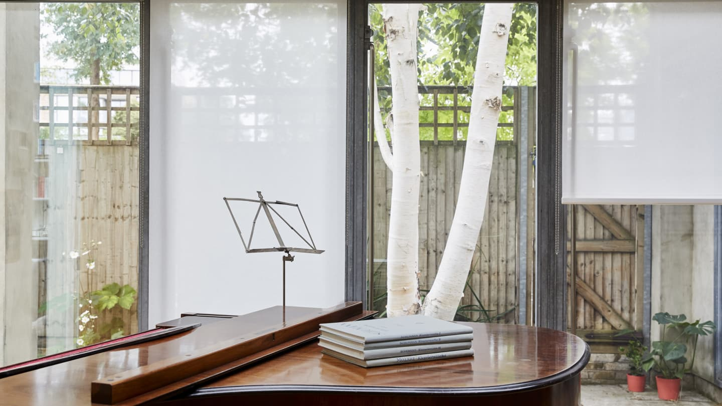 white linen blinds with piano in foreground
