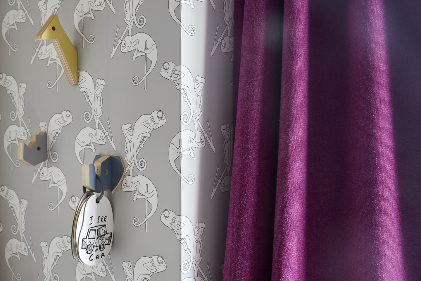chameleon wall paper and pink curtains close up