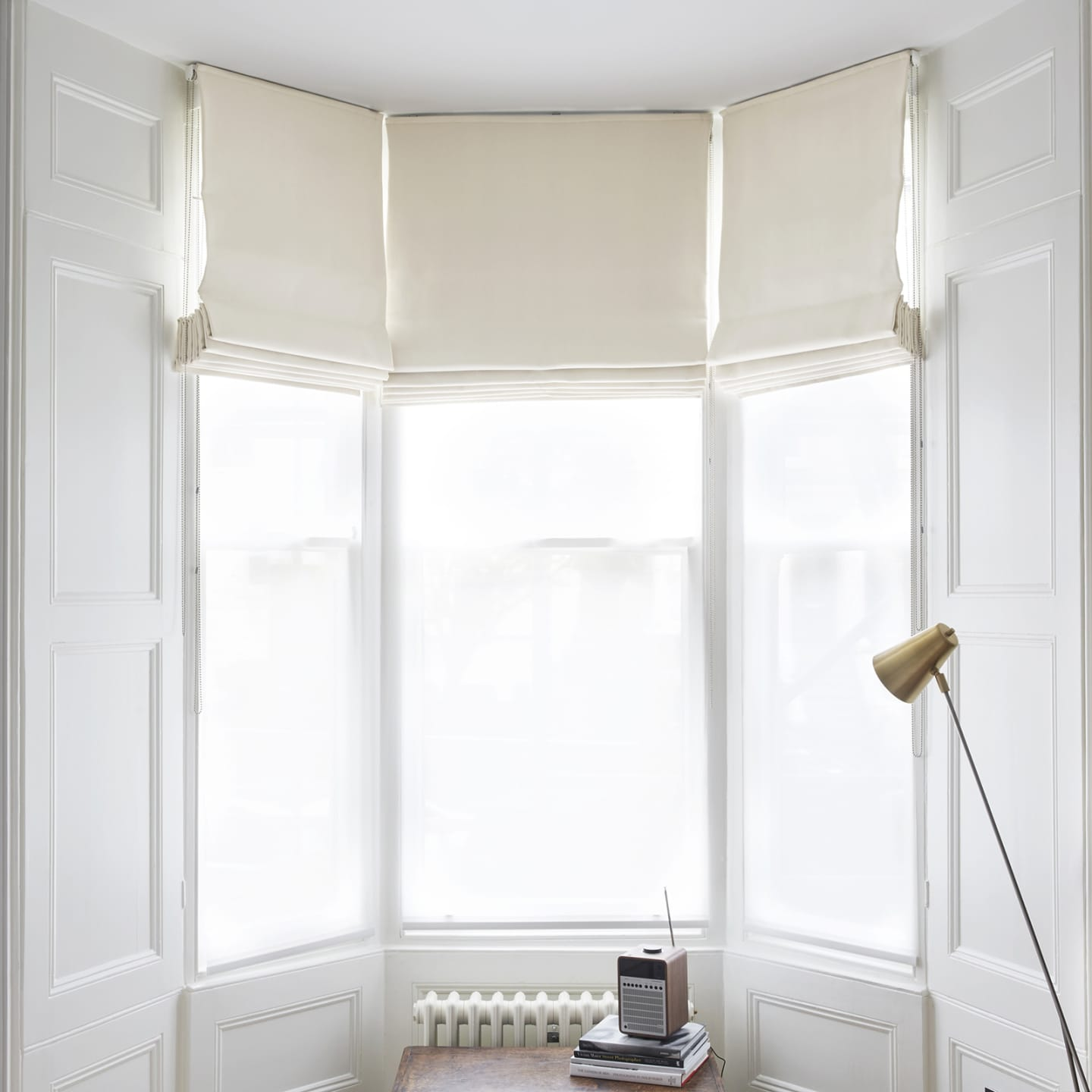 White bay windows with white roman blinds