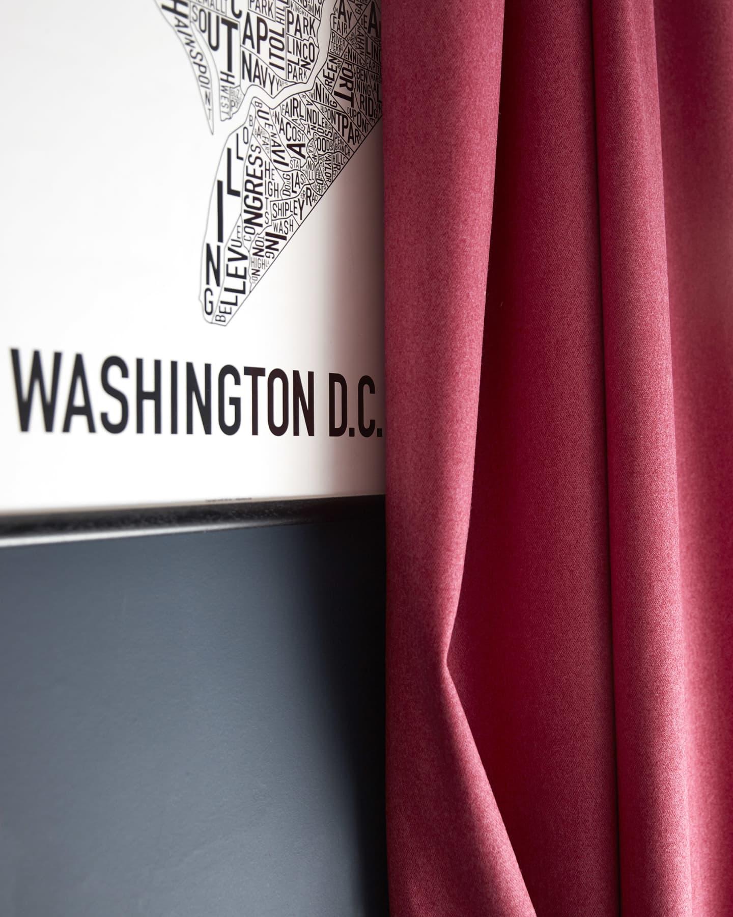 Pink woollen curtains against a dark wall