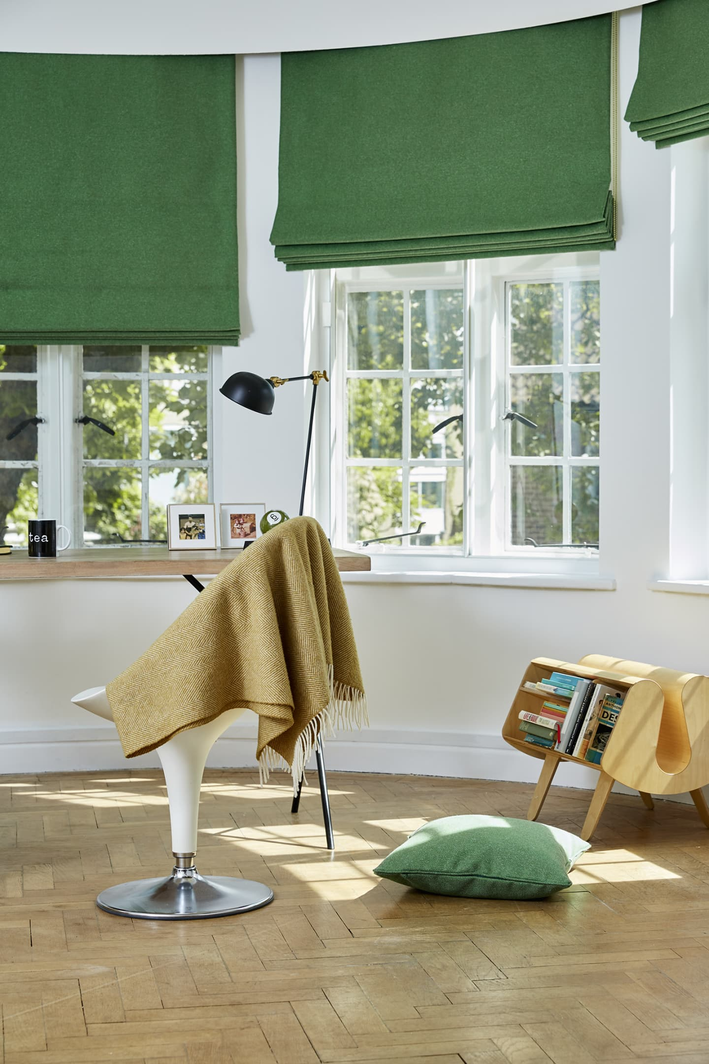 Bright study with three green woollen curtains
