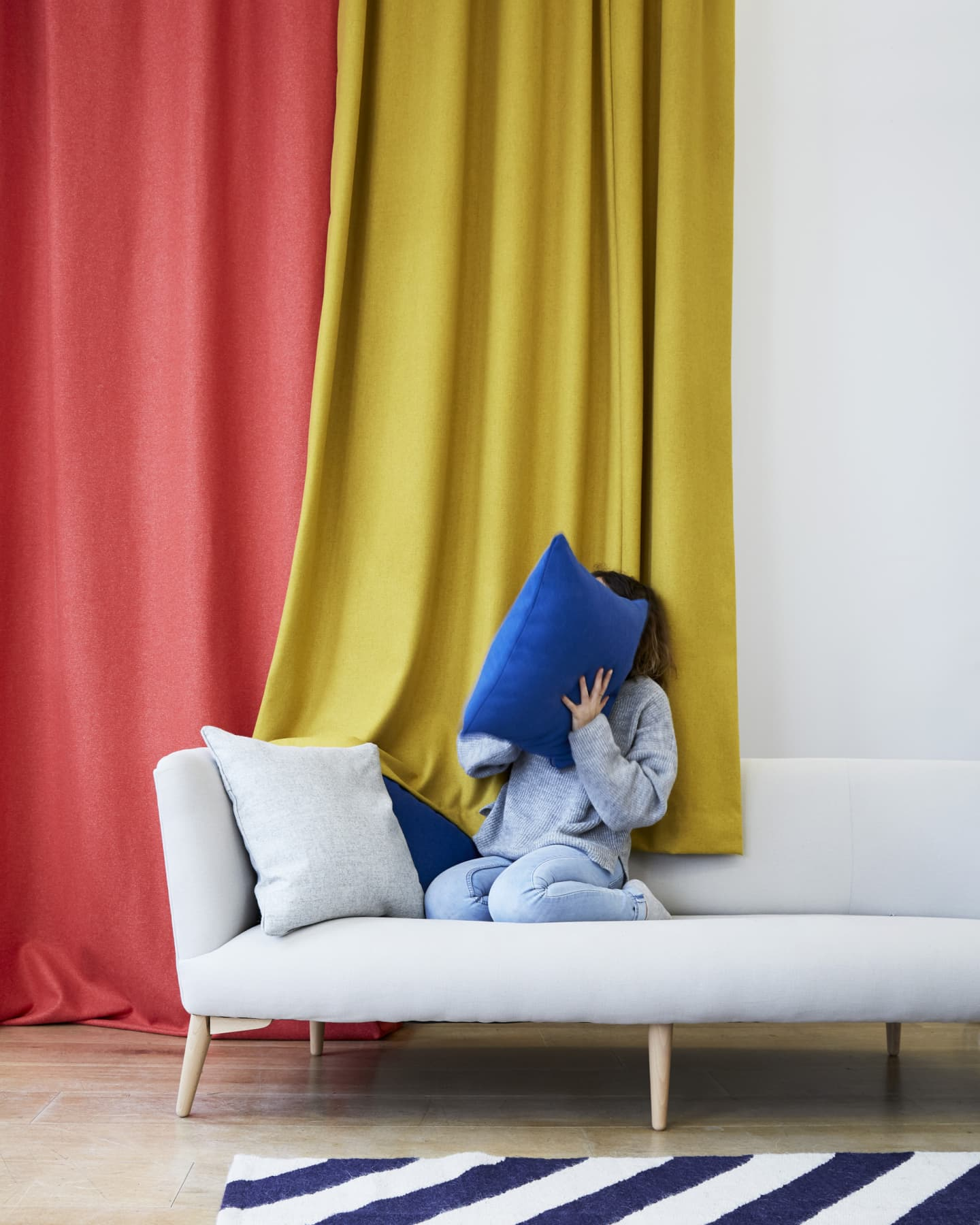 lady on a sofa with coloured cushions, curtains and rug