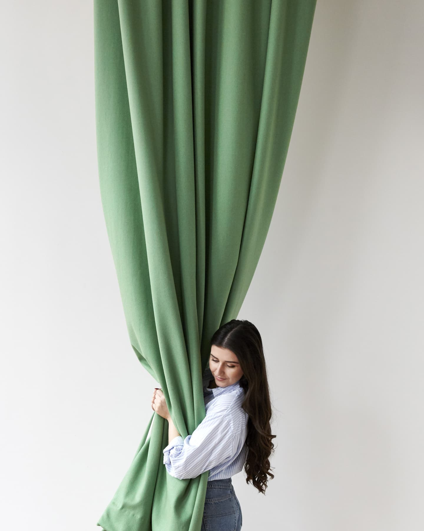 girl hugging a green curtain