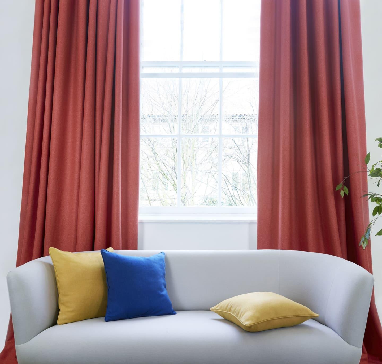 Red Curtains behind grey sofa