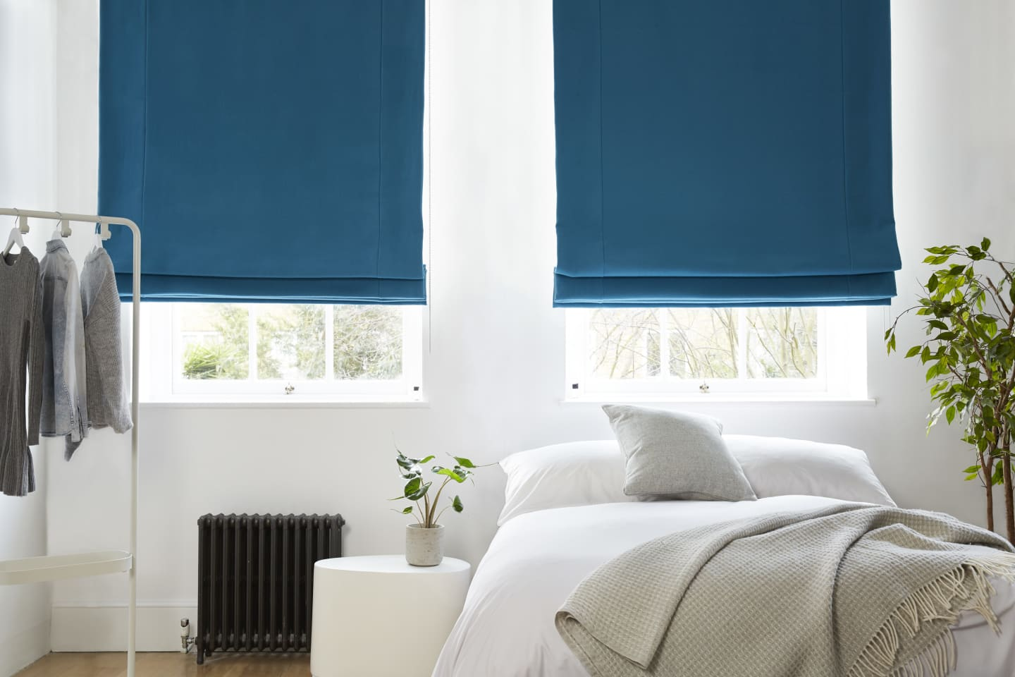 White bedroom with bright blue roman blinds