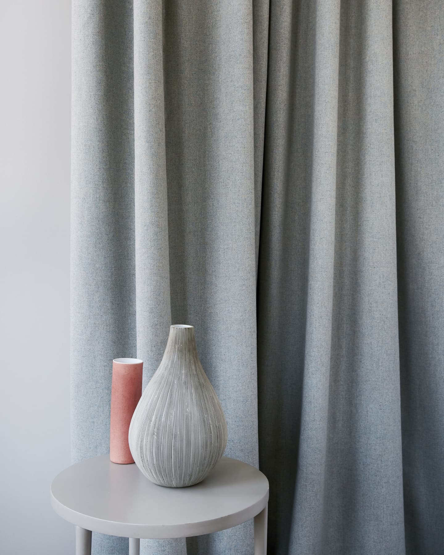 stood with ornaments and grey curtains behind