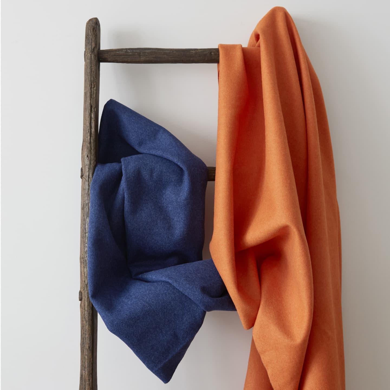 Orange and Blue wool fabrics hung on a ladder