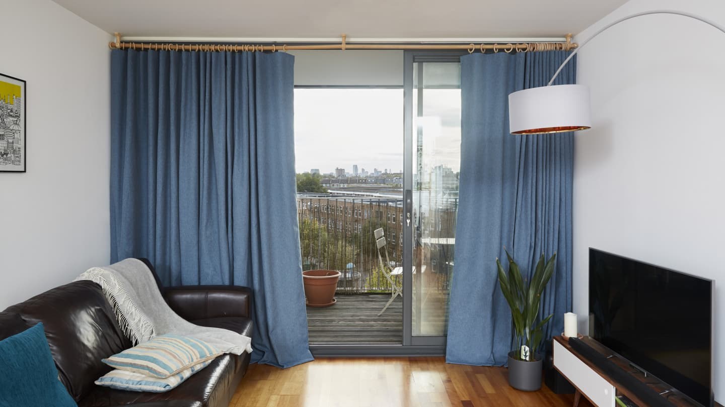 blue curtains in living room with balcony