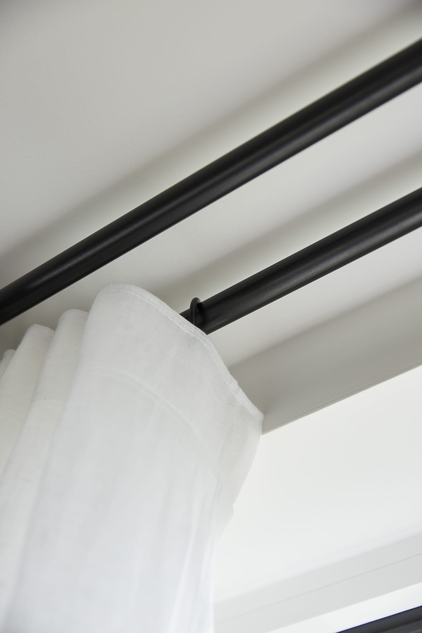 Close up of white linen curtain and track pole