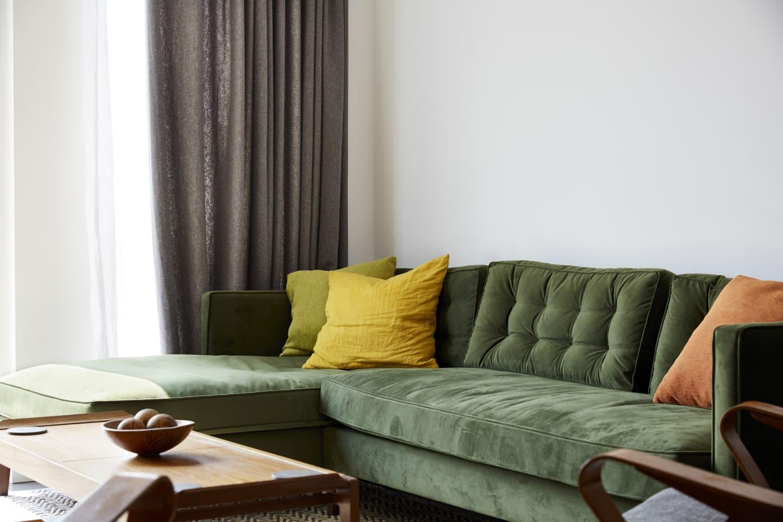 Green sofa with dark curtains behind