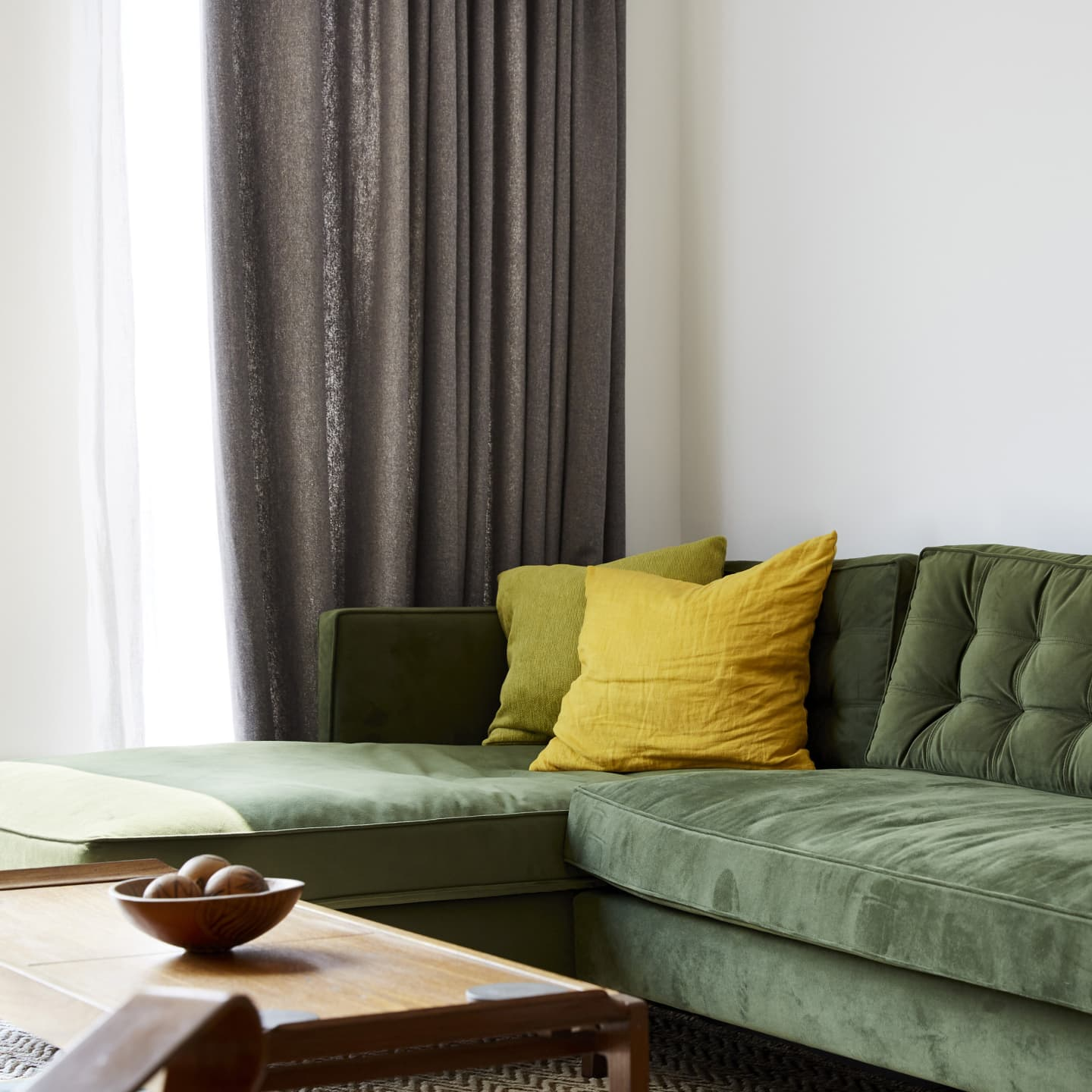 sofa with grey curtains in background