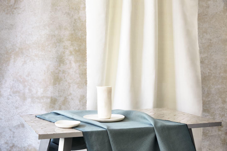 cream curtain hung and aqua textile on table
