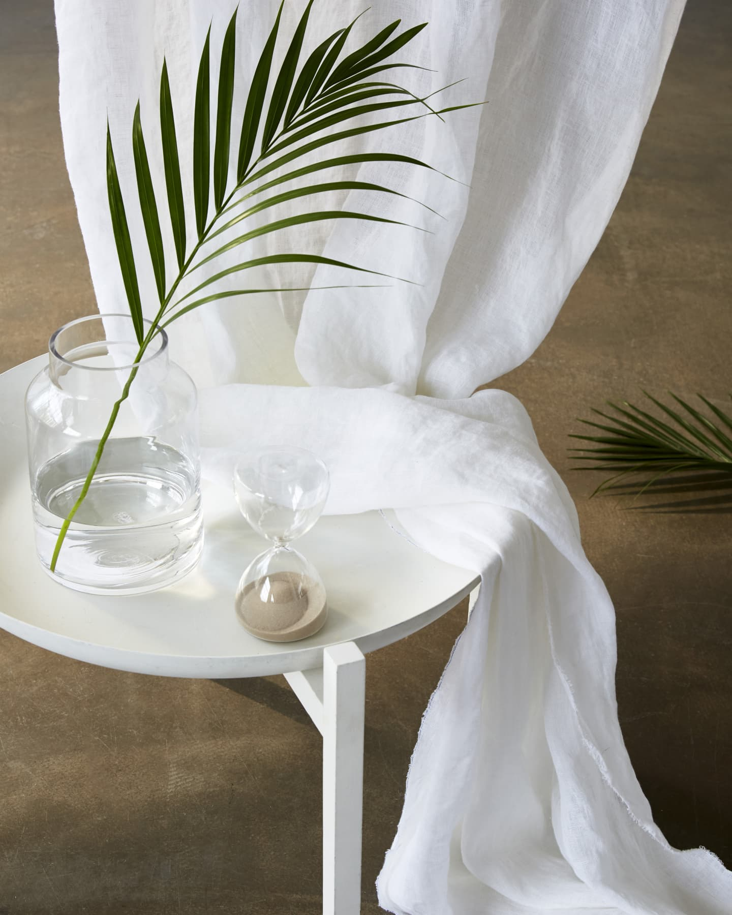 white linen curtain resting on a table