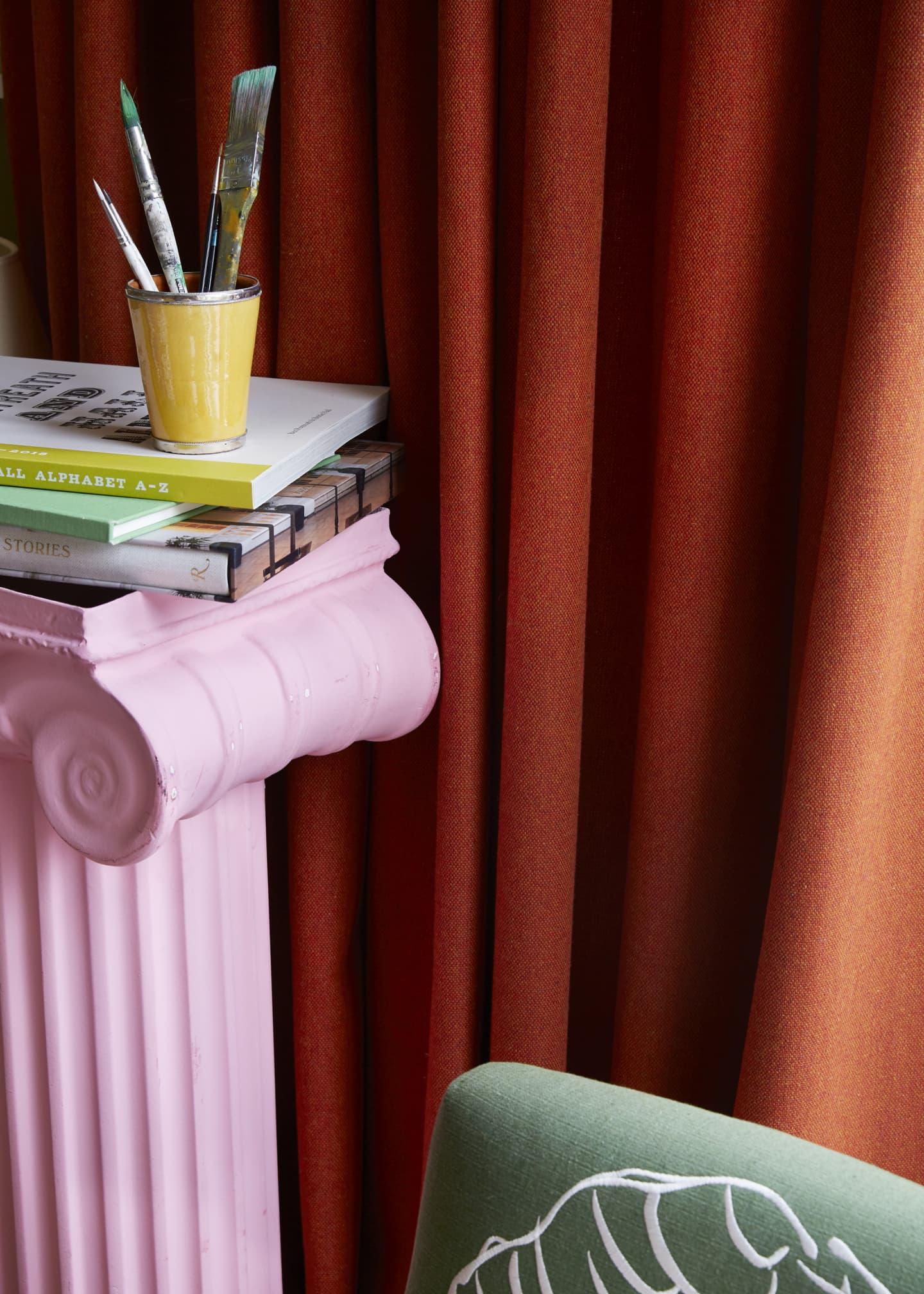 orange curtain behind pink pillar