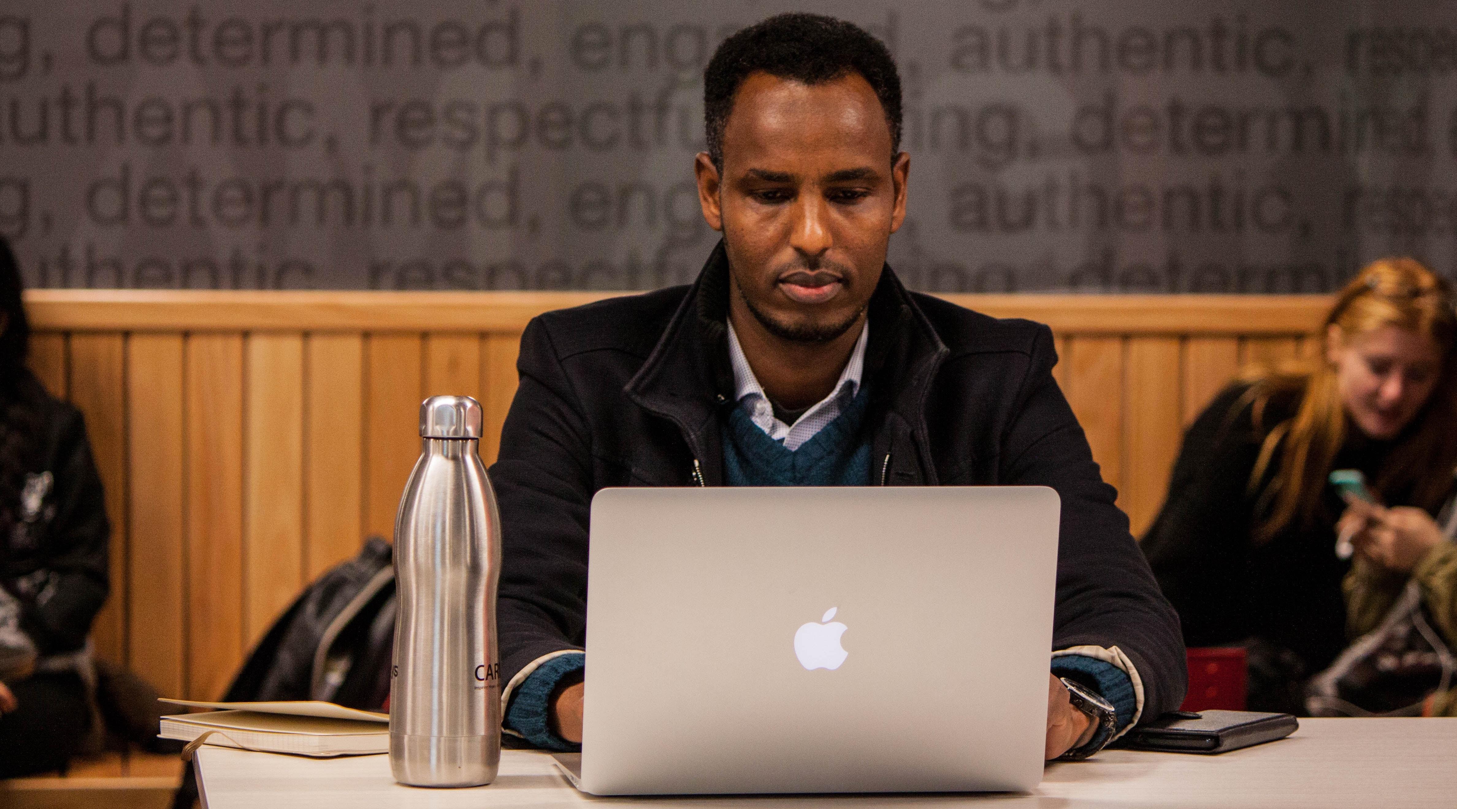 """Diversity in Tech, man programming on laptop - Photo by Trust """"Tru"""" Katsande on Unsplash"""