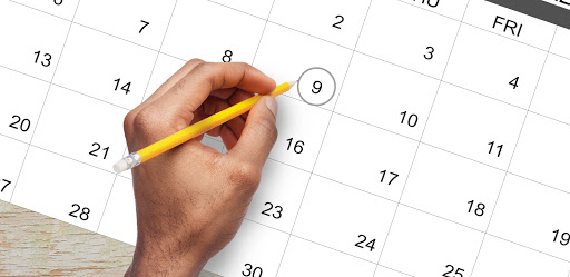 A hand with a pencil above a calendar