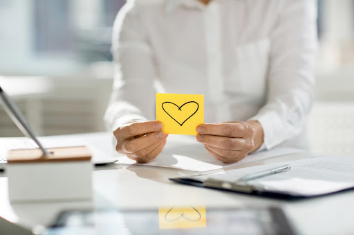 Person holding a sticky note with a heart