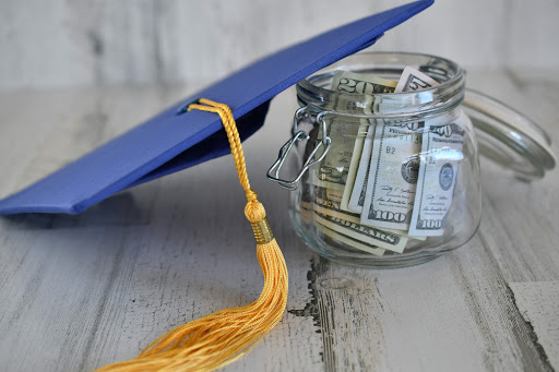 Graduation cap next to a jar of currency notes from the United States of America