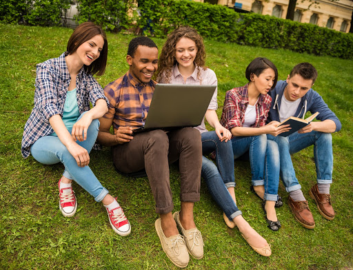 College students looking at a laptop on the grass