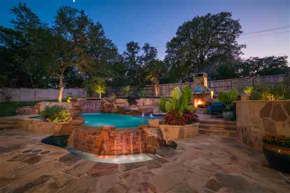 It was important to create a backyard oasis, with features reminiscent of the tropics, beckoning you to the vivid blue waters. As a final touch, lush landscaping and planter beds filled with banana ears and robust color soften the space, adding subtle ric