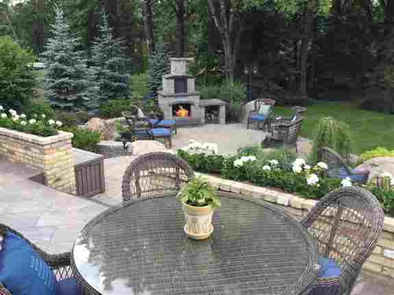 Multi level paving stone patio with stone fireplace and wood box.