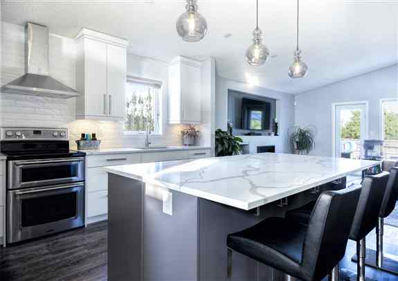 A much larger island than they previously had is great for entertaining!  The veining on the quartz countertops is gorgeous.