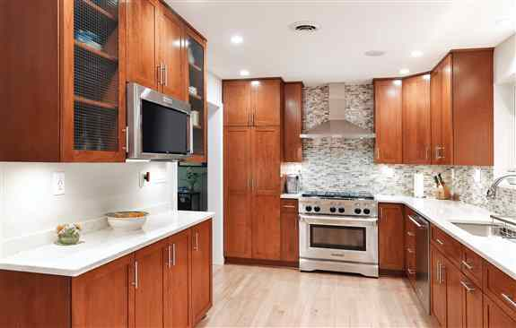 This kitchen in Kensington, MD was refaced with cherry wood and enriched with new conveniences including a lazy susan, wine rack, tip out tray and trash can pullout. The shaker style doors blend contemporary style with the warmth of cherry. The clean line