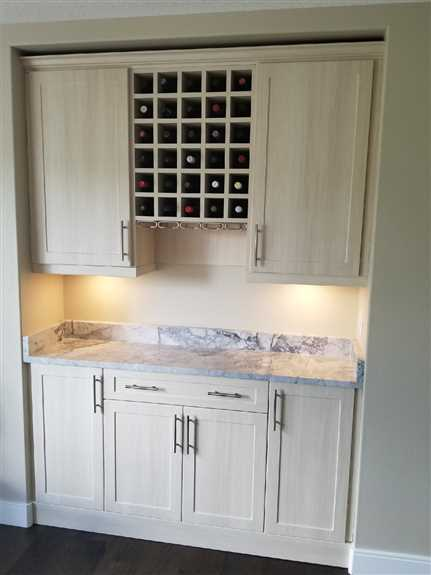We designed, built, and installed these custom thermofoil cabinets and wine rack to match the customer's existing kitchen cabinets.