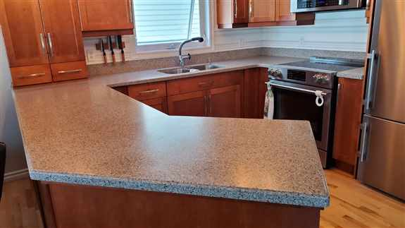 Our team designed and installed this new solid surface countertop with wall cladding.