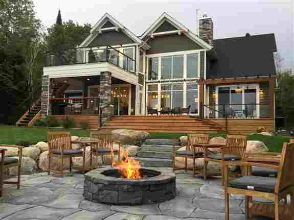 Belvadere fire pit and grand flagstone patio with rosetta steps and natural granite retaining walls provide a rugged and naturally beautiful area to enjoy evenings around the fire at this cabin in the Whiteshell.