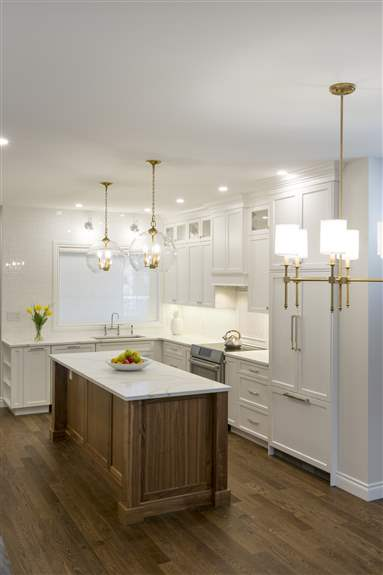Modern white kitchen complimented with a solid walnut island is pleasing to the eye.