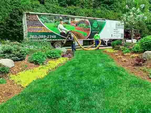 Action photo of blown-in landscape mulch using SylvaBark™.