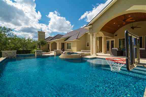 A stunning multi-level pool with a custom cut stone layered spa spillway and negative edge. Three chopped stone pedestals bring a touch interest to the transition from the upper pool to the lower pool area. This unique design allowed for two separate spac
