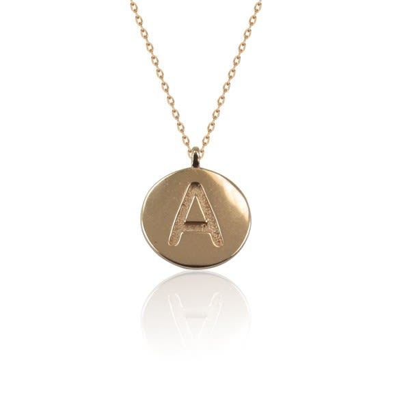 A delicate chain suspends a disc pendant with a letter engraving detail. Initial necklace in sterling silver with three color options: silver, rose gold, gold.