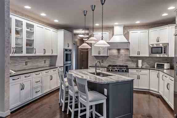 The mixture of white and gray cabinets and countertops creates the perfect balance of contemporary elements. Elegantly curved brushed nickel hardware and faucets soften the square shaker style doors. A solid gray quartz countertop paired with white cabine