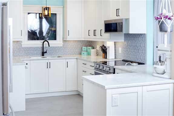 Lots of wonderful options for backsplashes.  This grey hexagon backsplash looks amazing with the white cabinets and countertop.  And the teal wall colour and vintage canister set!