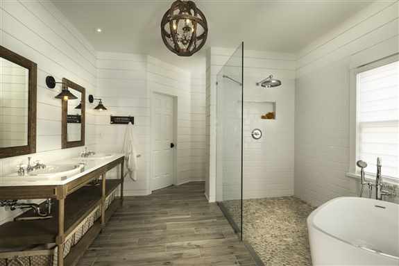 European style bath with open shower / tub combo wet area and open cabinets.