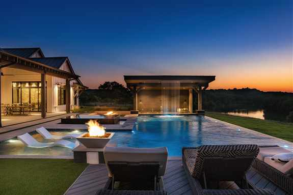 A stunning, lakefront contemporary outdoor space that exudes elegance and function with captivating views. The negative edge linear pool boasts an over-sized sun shelf with bubblers, a negative edge glass tiled spa, fire bowls, and a dramatic water featur