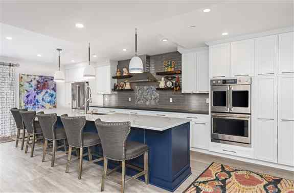 This two-tone white and blue maple kitchen was expanded and refaced by Kitchen Saver. The cabinets were expanded with 4 floating shelves, and access to storage was increased by installing full extension drawer slides and rollouts. Specialized storage like