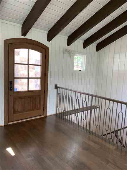 Arched front door and modern balusters and rails